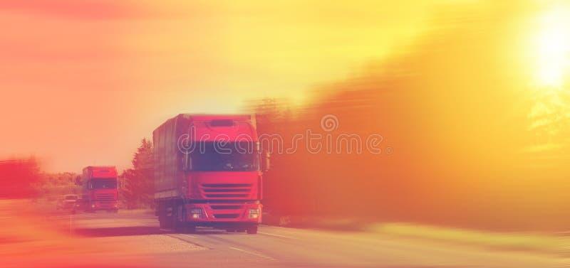 Verschepend twee rode ladingsvrachtwagens op de weg die de zonsondergang gele avond van de stralenzon worden gedreven royalty-vrije stock foto