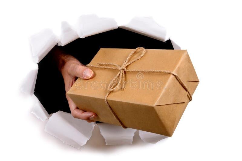 Verschicken Sie den Mann oder Briefträger, die Paket durch heftigen Weißbuchhintergrund liefern oder geben stockfotografie