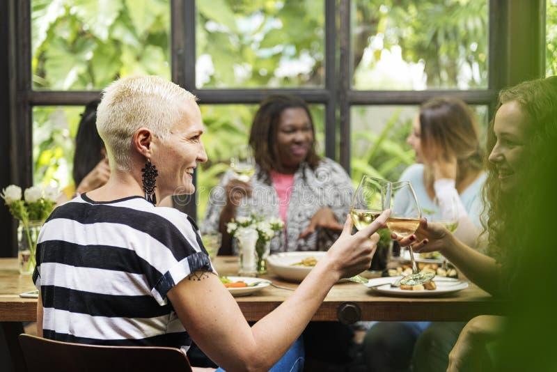 Verschiedenartigkeits-Frauen-Gruppe, die Konzept zusammen essend hängt stockbilder
