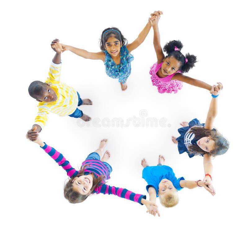Verschiedenartigkeits-Kinder, welche die Handfreundschaft spielt Konzept halten lizenzfreie stockfotografie