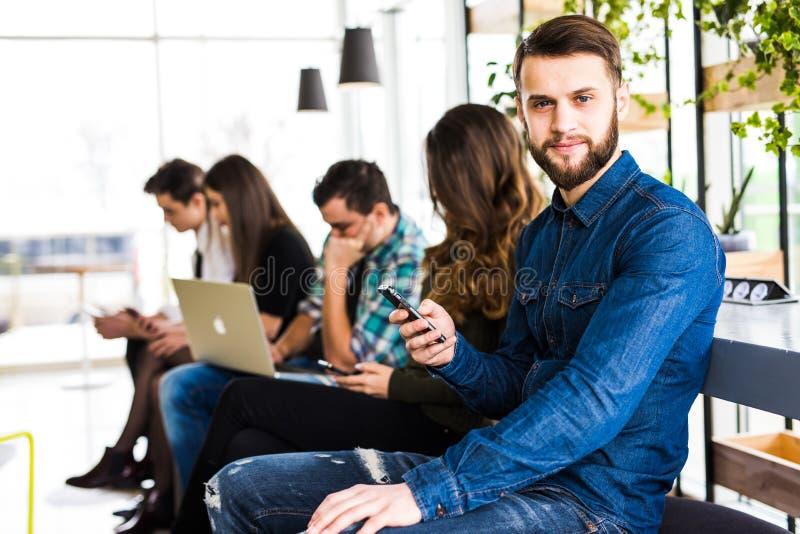 Verschiedenartigkeits-Leute-Verbindungs-Digital-Geräte, die Konzept grasen freunde Fokus auf erstem bärtigem Lächelnmann lizenzfreies stockfoto