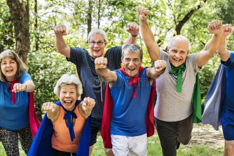 Verschiedene ältere tragende Superheldkleidung, die Spaß im Park hat lizenzfreies stockbild