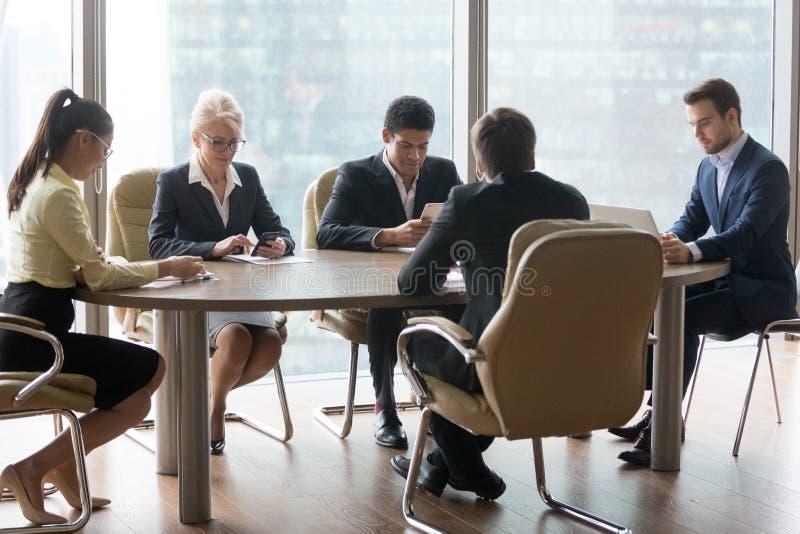 Verschiedene Angestellte, die Geräte während der Geschäftslokalsitzung verwenden lizenzfreies stockfoto
