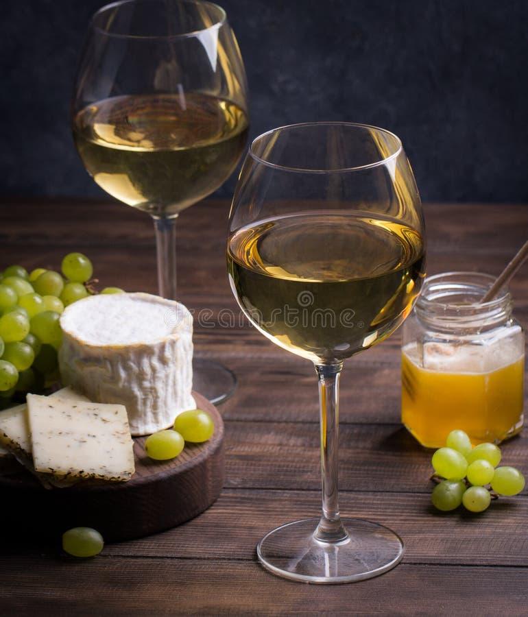 Verschiedene Art des Käses, der Trauben und zwei Gläser des Weißweins stockbilder