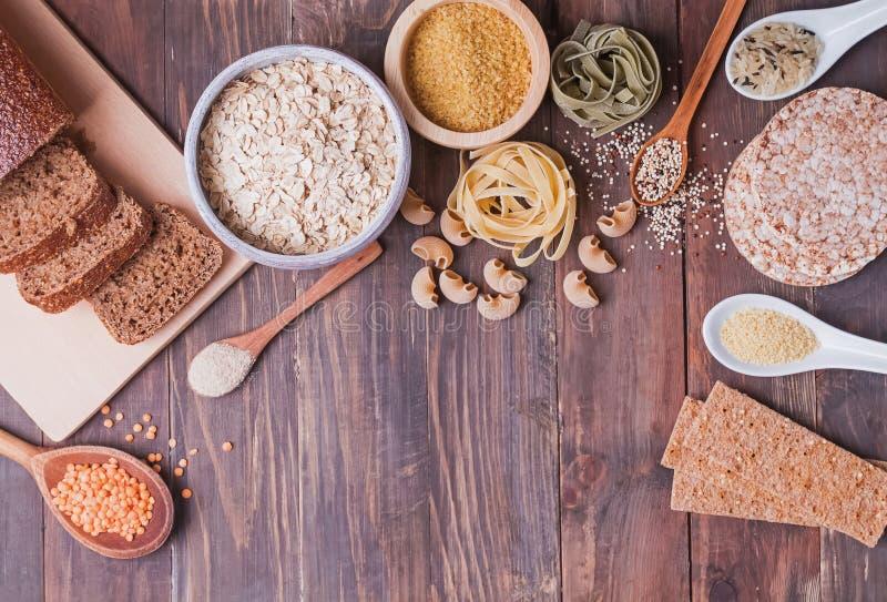 Verschiedene Arten der hohen Kohlenhydratnahrung auf dem hölzernen Hintergrund lizenzfreies stockfoto