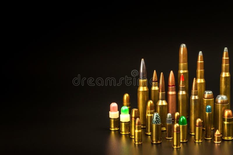 Verschiedene Arten der Munition auf einem schwarzen Hintergrund Verkauf von Waffen und von Munition Das ri lizenzfreie stockfotografie