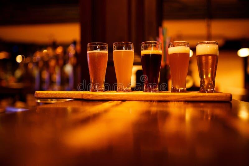 Verschiedene Arten des Handwerksbieres in den kleinen Gläsern auf einem Holztisch in einer Kneipe stockfotografie
