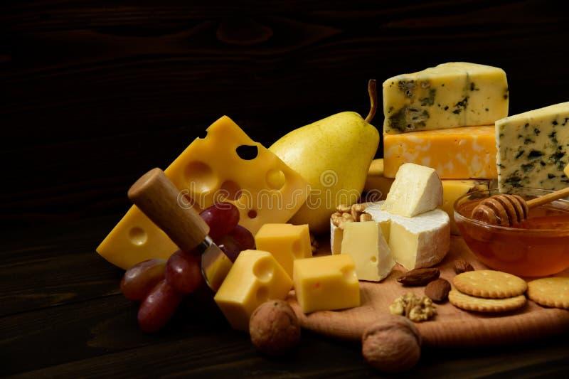 Verschiedene Arten des Käses auf einem rustikalen Holztisch lizenzfreies stockbild