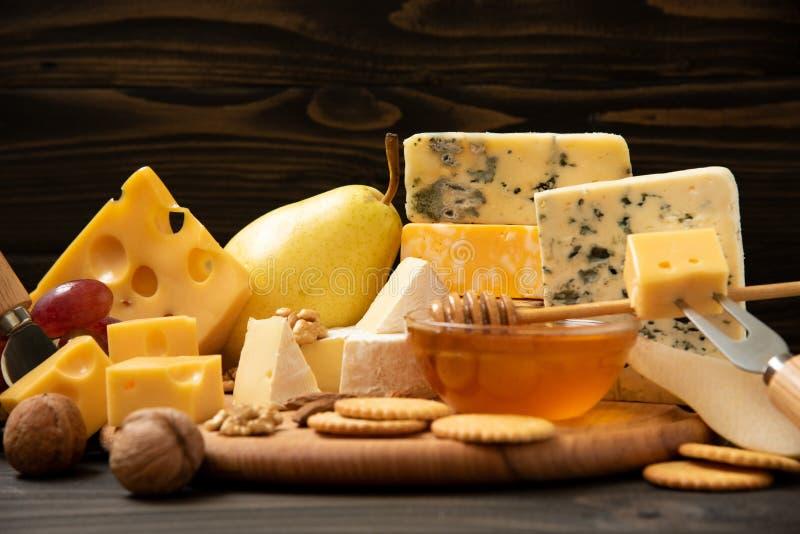 Verschiedene Arten des Käses auf einem rustikalen Holztisch lizenzfreie stockfotografie