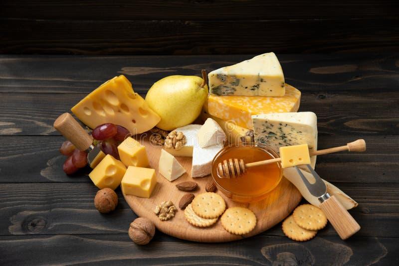 Verschiedene Arten des Käses auf einem rustikalen Holztisch stockbilder