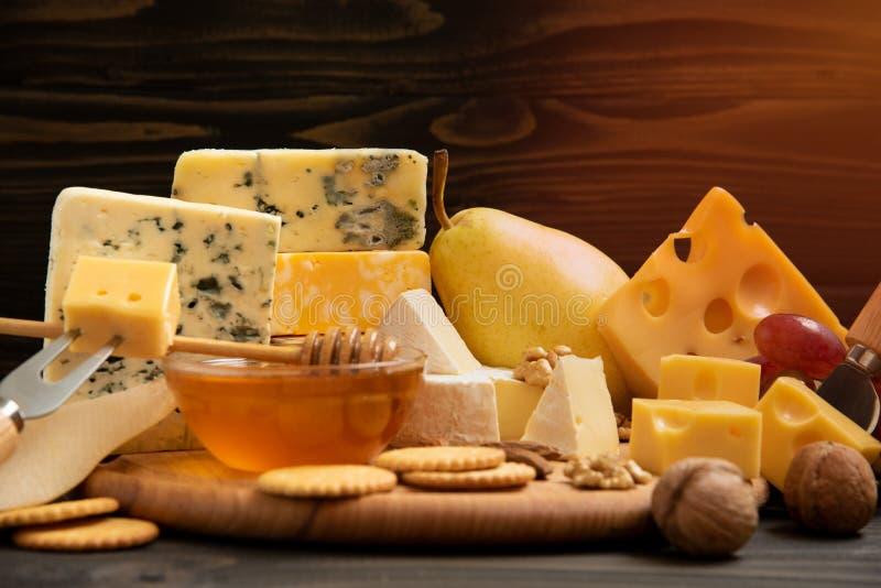 Verschiedene Arten des Käses auf einer rustikalen Tabelle lizenzfreie stockbilder