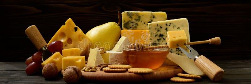Verschiedene Arten des Käses auf einer rustikalen Tabelle stockfotografie