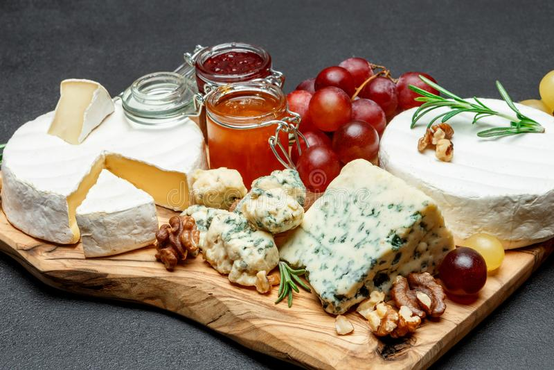 Verschiedene Arten des Käses und des Staus auf hölzernem Schneidebrett lizenzfreies stockfoto