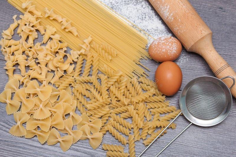 Verschiedene Arten oder rohe italienische Teigwaren auf dem hölzernen rustikalen Hintergrund und Bestandteile für Teigwaren Drauf lizenzfreie stockfotografie