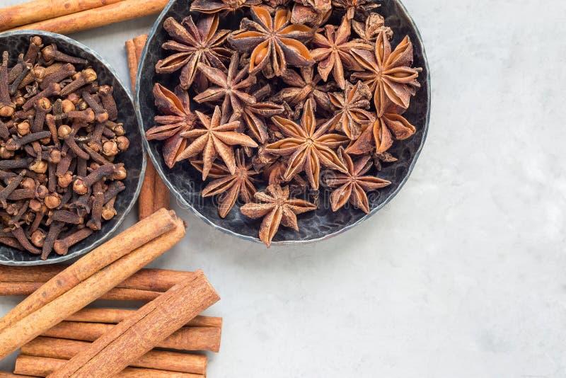 Verschiedene Arten von aromatischen Wintergewürzen in den Schüsseln und auf einem grauen konkreten Hintergrund, Draufsicht, Kopie stockfotos