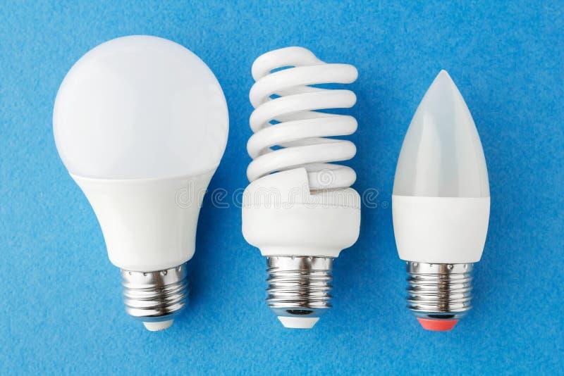 verschiedene Arten von energiesparenden Lampen auf einem blauen Hintergrund stockfoto