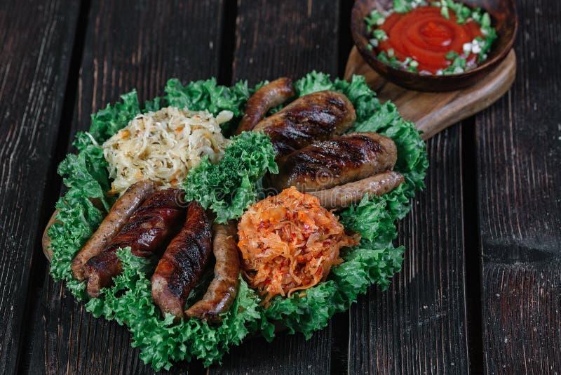 Verschiedene Arten von gegrillten gebratenen Würsten mit gedämpftem Kohl und Sauerkraut lizenzfreies stockfoto