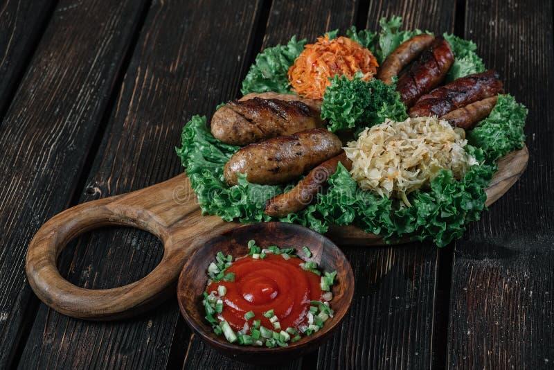 Verschiedene Arten von gegrillten gebratenen Würsten mit gedämpftem Kohl und Sauerkraut stockbild