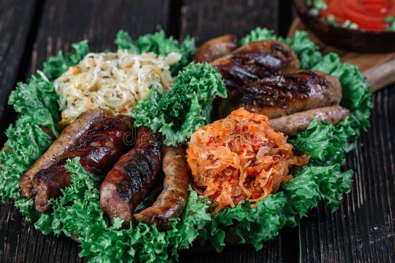 Verschiedene Arten von gegrillten gebratenen Würsten mit gedämpftem Kohl und Sauerkraut stockfotos