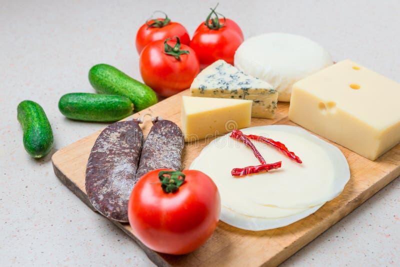 Verschiedene Arten von Käsen, mit Trockenfleisch, Tomaten, Gurke lizenzfreie stockbilder