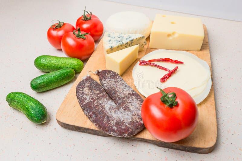 Verschiedene Arten von Käsen, mit Trockenfleisch, Tomaten, Gurke lizenzfreies stockbild