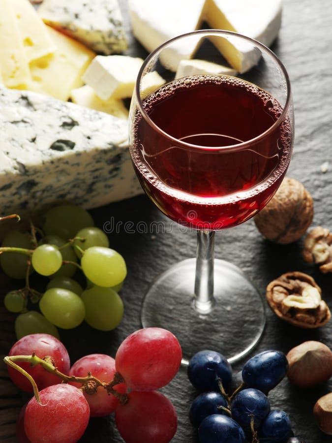 Verschiedene Arten von Käsen mit Weinglas und -früchten stockbild
