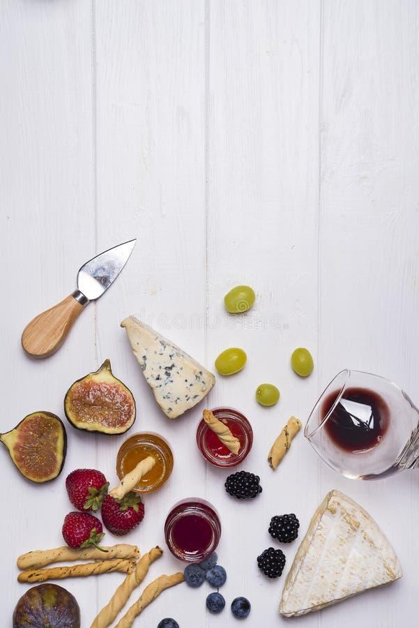 Verschiedene Arten von Käsen mit Weinglas und -früchten lizenzfreie stockbilder