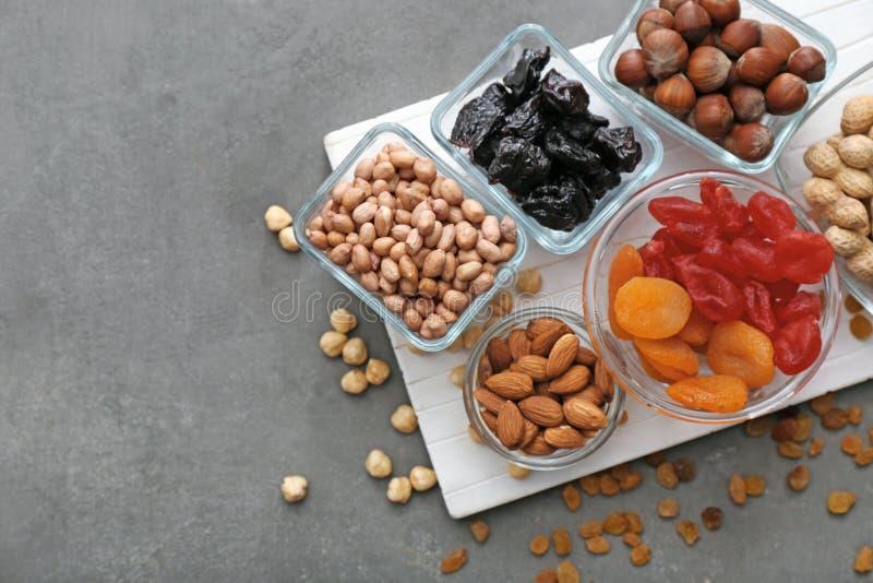 Verschiedene Arten von Nüssen und von Trockenfrüchten in den Schüsseln auf Tabelle stockbild