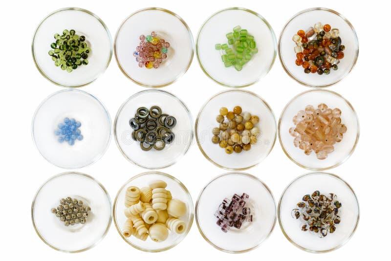 Verschiedene Arten von Perlen; auf Weiß in den kleinen Glasschüsseln stockfotografie