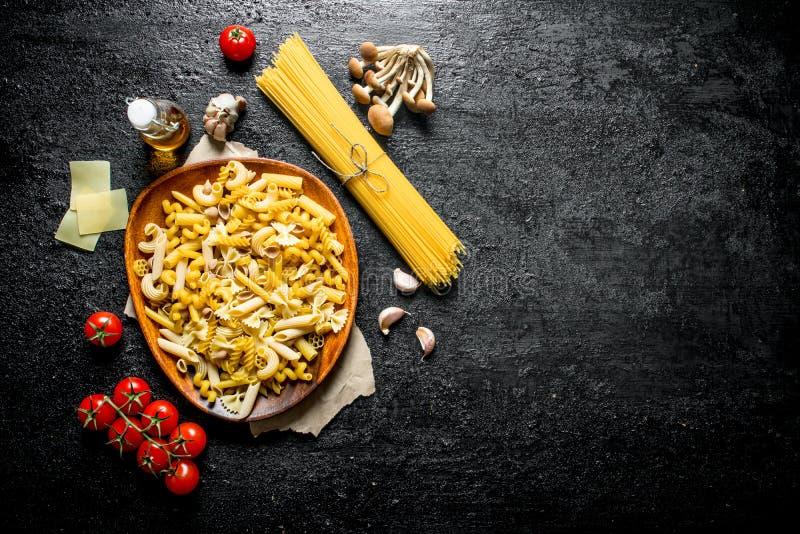 Verschiedene Arten von rohen Teigwaren mit K?sescheiben, -pilzen und -tomaten stockfotografie