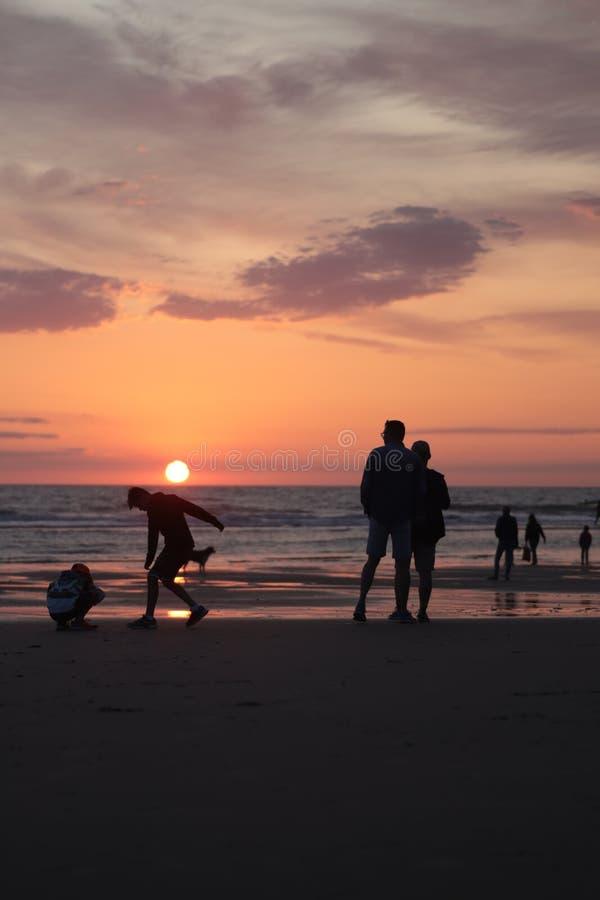 Verschiedene Arten von silouette Leuten am Strand während eines schönen Sonnenuntergangs in Frankreich-montalivet lizenzfreies stockfoto