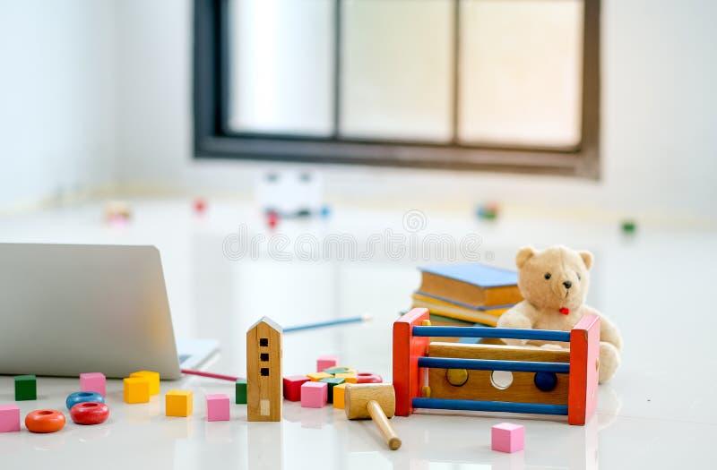Verschiedene Arten von Spielwaren und von Puppe werden auf den Boden nahe zur Laptop-Computer vor Glasfenstern gesetzt stockbilder