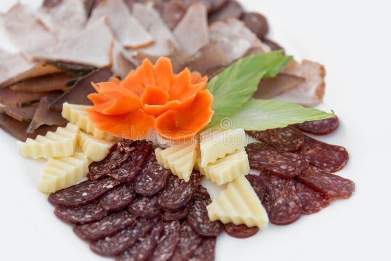 Verschiedene Arten Zartheit des Fleisches und des Käses vereinbarten in einer Platte über hellem Hintergrund stockbild