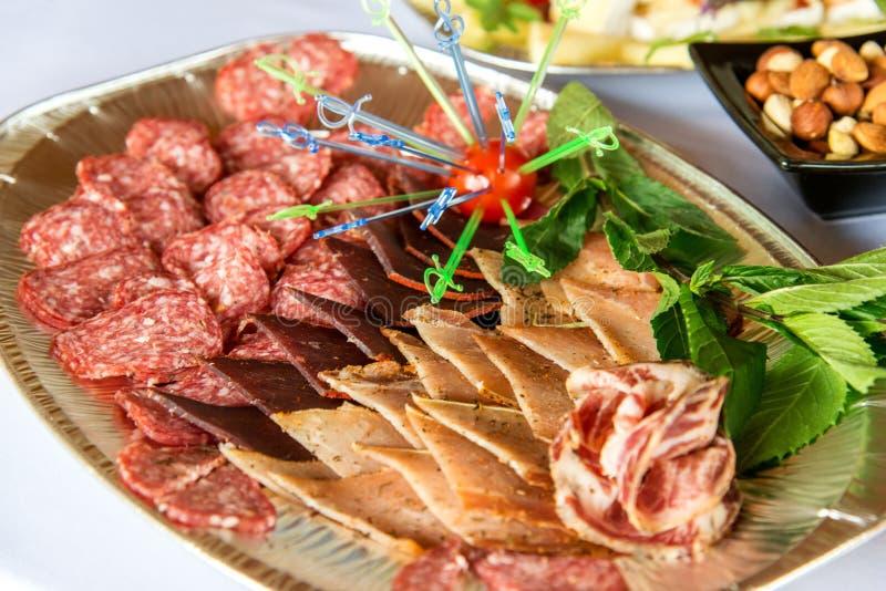 Verschiedene Arten Zartheit des Fleisches und des Käses vereinbarten in einer Platte über hellem Hintergrund lizenzfreies stockbild