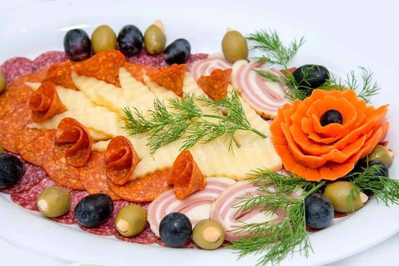 Verschiedene Arten Zartheit des Fleisches und des Käses vereinbarten in einer Platte über hellem Hintergrund stockbilder