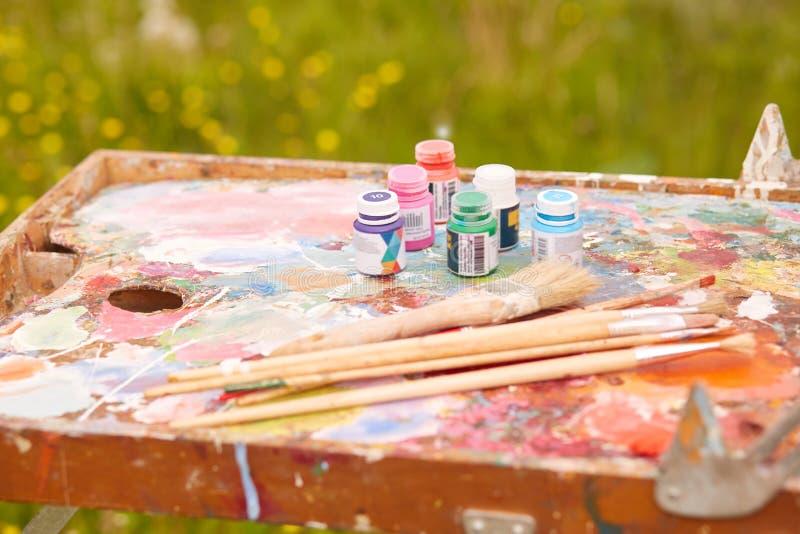 Verschiedene Ausrüstungen für das Zeichnen und mischt Ölfarben, Mischungsvorgangfarben auf Palette, Rohre und Bürsten auf scketch lizenzfreie stockbilder