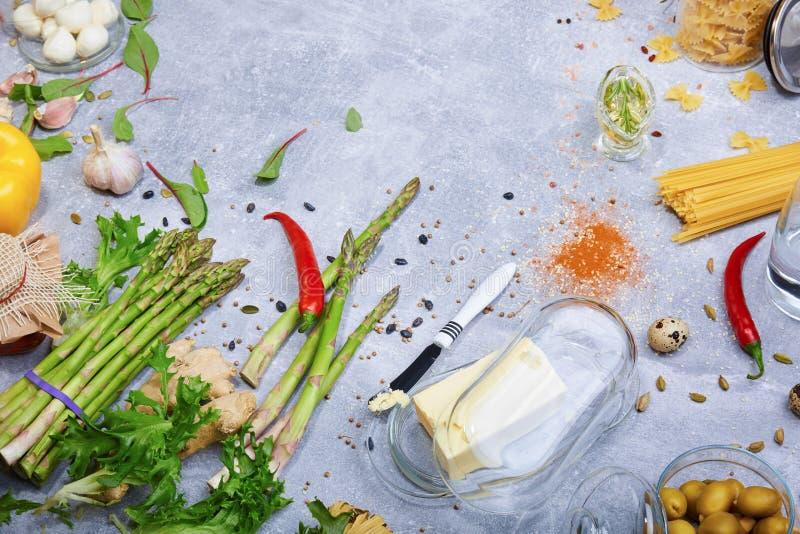Verschiedene Bestandteile auf einem Tabellenhintergrund Butter mit einem Messer und Gewürzen Neue Grüns und Pfeffer Teigwarenvorb lizenzfreies stockbild
