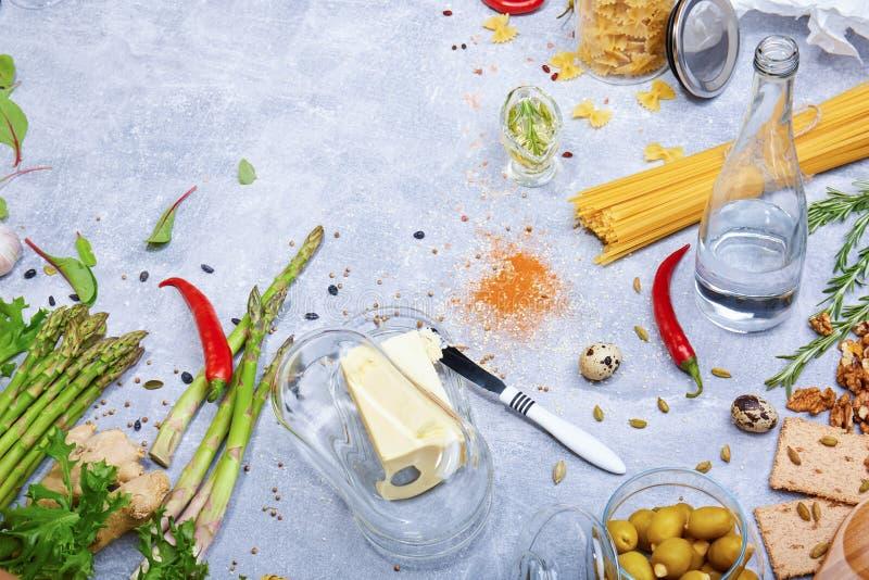 Verschiedene Bestandteile auf einem Tabellenhintergrund Butter mit einem Messer und Gewürzen Neue Grüns und Pfeffer Teigwarenvorb stockbild