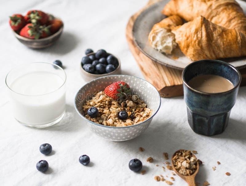 Verschiedene Bestandteile für selbst gemachtes Granola, Hörnchen, Beeren, Kaffee mit Milch, Honig und Jogurt des Frühstücks stockbild