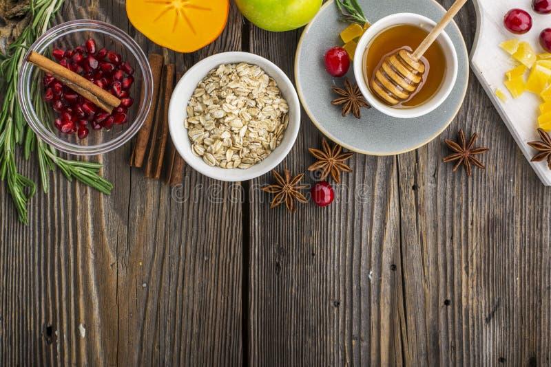Verschiedene Bestandteile für Wintersaisonbacken und andere Rezepte, Granatapfel, Honig, orezhi, Äpfel, Persimonen, Kräuter stockfoto