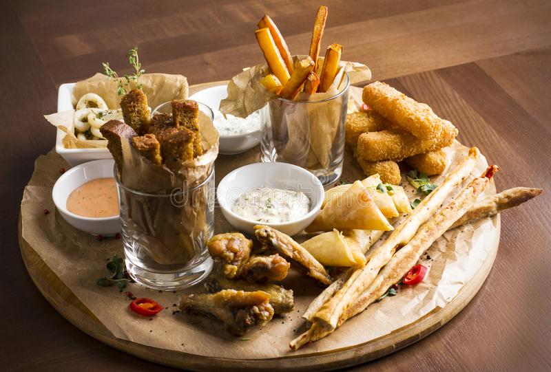 Verschiedene Biersnäcke: Calamariringe, Fischrogen, heiße Flügel, Brot stockfoto