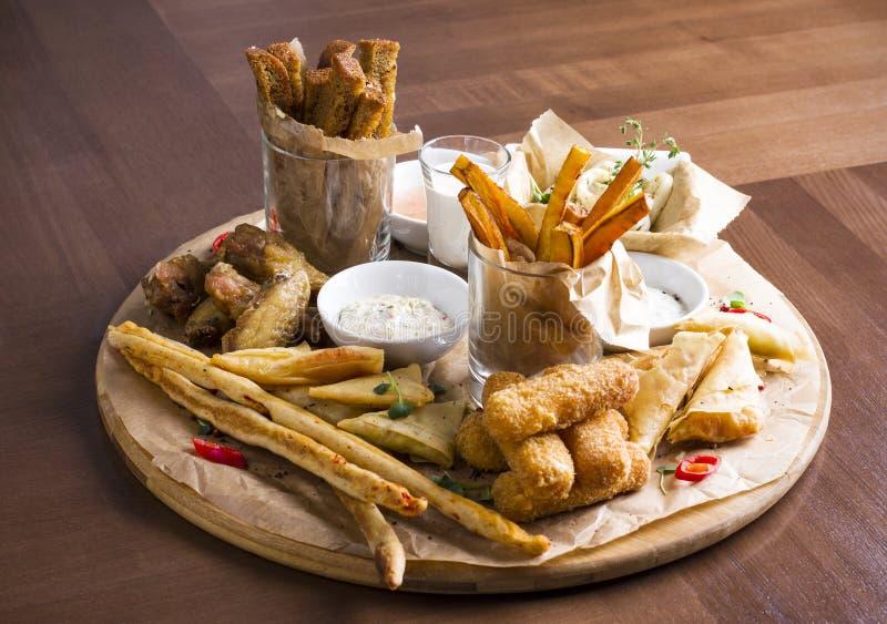 Verschiedene Biersnäcke: Calamariringe, Fischrogen, heiße Flügel, Brot stockbild