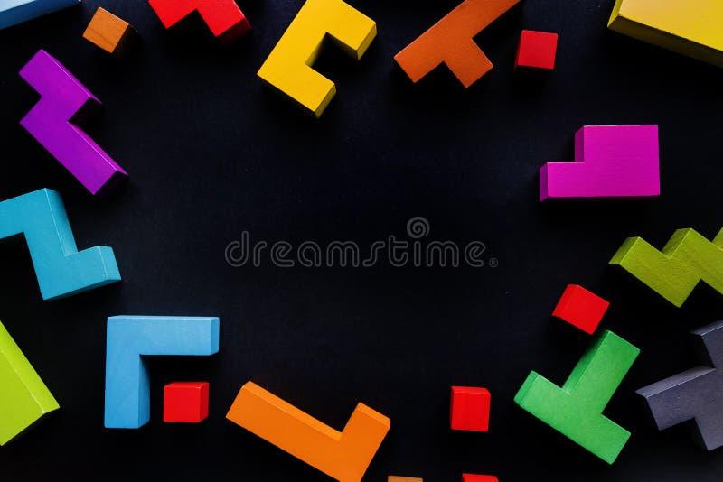 Verschiedene bunte Formholzklötze auf schwarzem Hintergrund, flache Lage Geometrische Formen in den verschiedenen Farben, Draufsi lizenzfreies stockbild