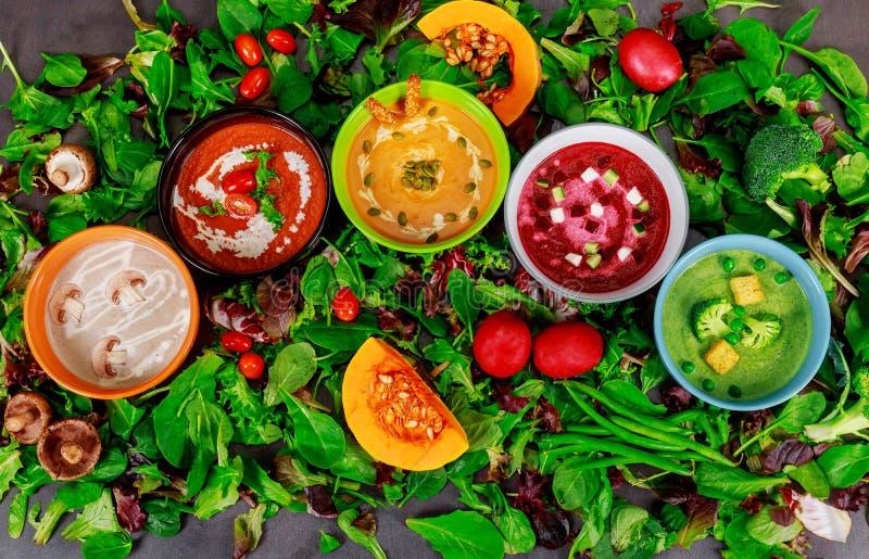 Verschiedene bunte Gemüsesahnesuppen in Schüsseln, Essen oder vegetarische Nahrung stockfotos