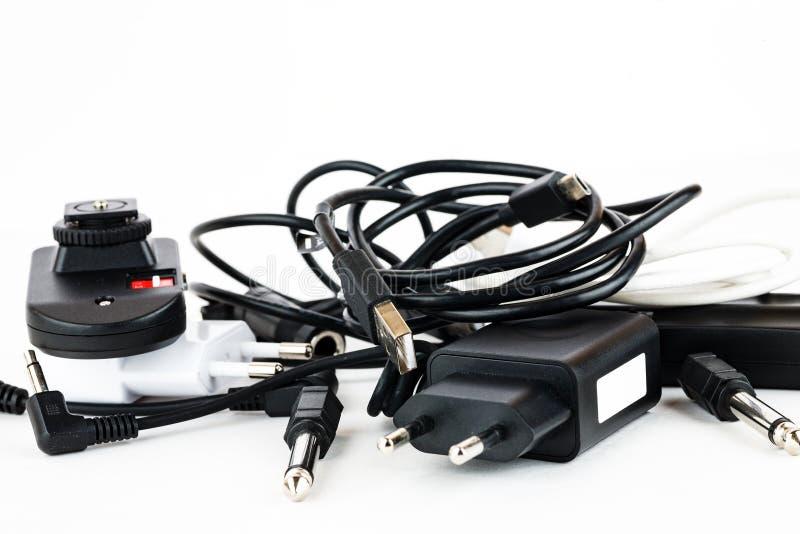 Verschiedene Drähte und Verbindungsstücke auf einem weißen Hintergrund, Ausrüstungsverwirrung stockbilder