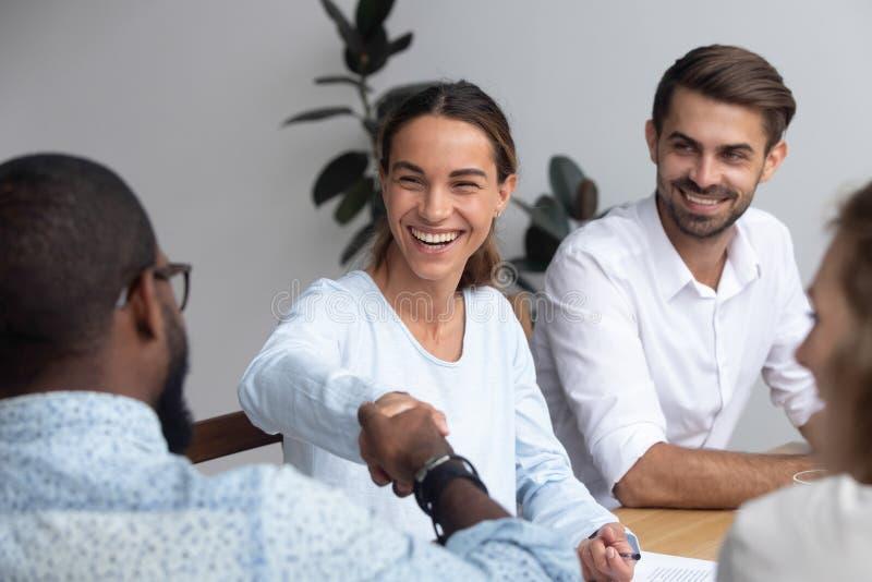 Verschiedene erfolgreiche Geschäftsleute, die Hände während des Geschäfts rütteln stockbilder