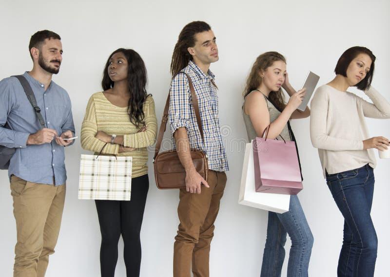 Verschiedene ethnische Leute in einer Linie Aufwartung stockfoto