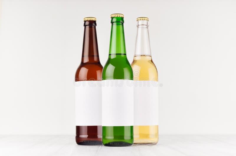 Verschiedene Farben der Bierflaschen 500ml mit leerem weißem Aufkleber auf weißem hölzernem Brett, verspotten oben Schablone für  stockfoto