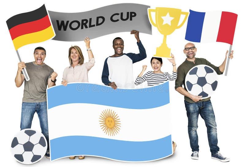 Verschiedene Fußballfane, welche die Flaggen von Argentinien, von Deutschland und von Frankreich halten stockbilder
