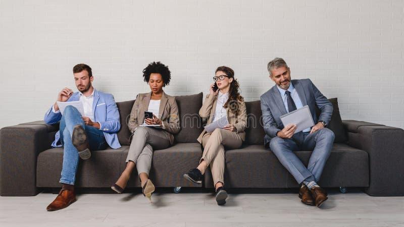 Verschiedene Geschäftsleute, die auf ein Interview warten stockfotos